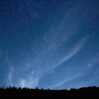 Blauwe donkere nachthemel met vele sterrenachtergrond
