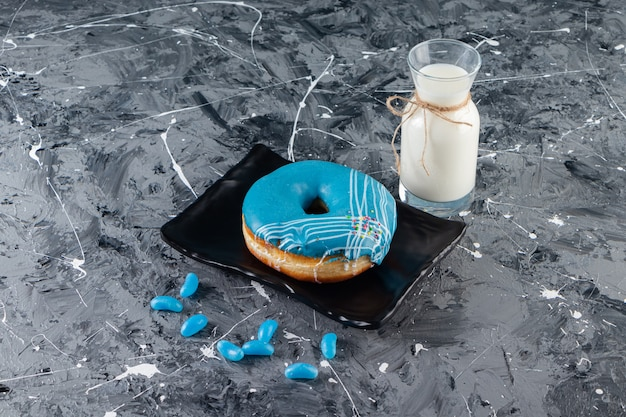 Blauwe donut met slagroom glazuur en glas melk op marmeren tafel.