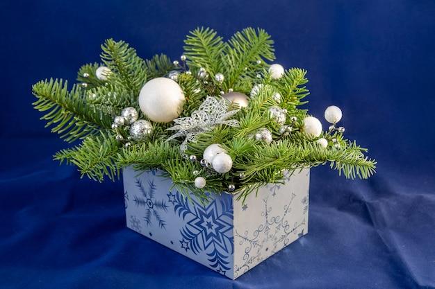 Blauwe doos met dennenappels en witte ballen kerstboom nieuwjaarskerstversieringen