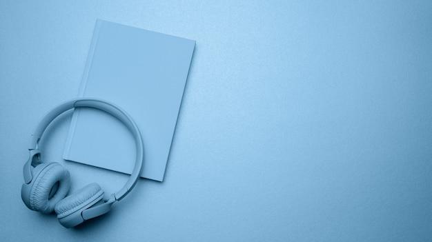 Blauwe draadloze hoofdtelefoons en een gesloten blocnote. bovenaanzicht