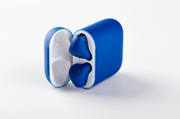Blauwe draadloze koptelefoon airpods in oplaadcase close-up