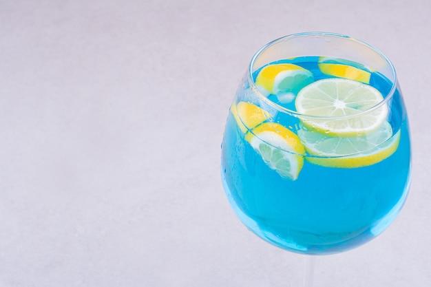 Blauwe drank met schijfjes citroen erin.