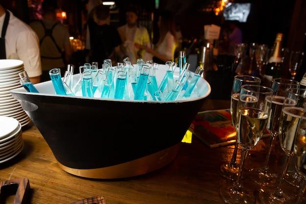 Blauwe drankjes in een bekerglas in een emmer met ijs