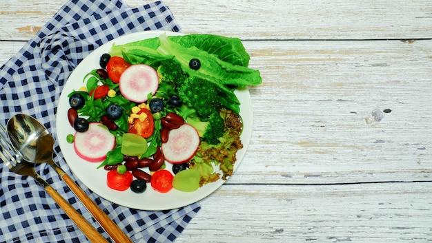 Blauwe druivenwijngaarden, rode bonen, tomaten, currypinda's, fornuizen, dinergerechten, gezondheidszorg in borden, geplaatst met lepels en reparaties, geplaatst op schots weefsel, houten tafel