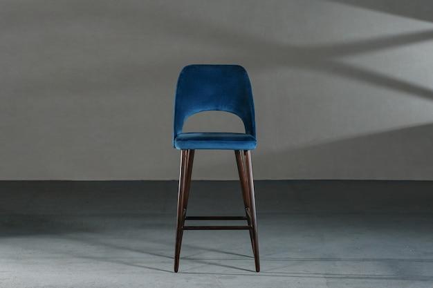 Blauwe eetkamerstoel in een studio met grijze muren