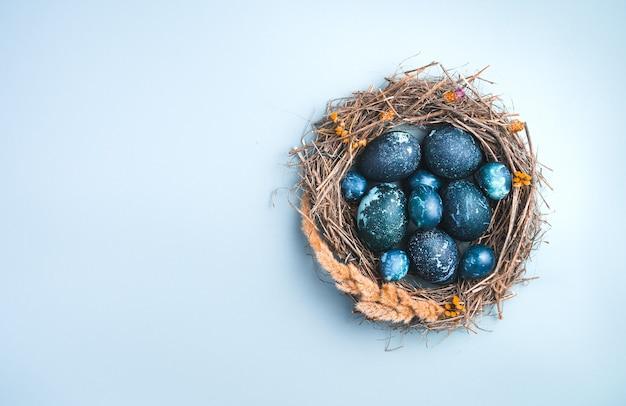 Blauwe eieren in een nest op een blauwe achtergrond. bovenaanzicht, met ruimte om te kopiëren. het concept van pasen.