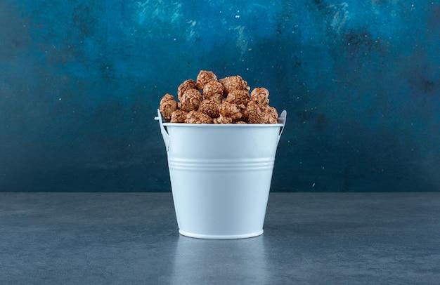 Blauwe emmer gevuld met popcornsuikergoed op blauw