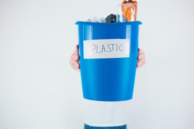Blauwe emmer met plastic. klaar voor recycling en milieuproces. zorg voor ecologie.