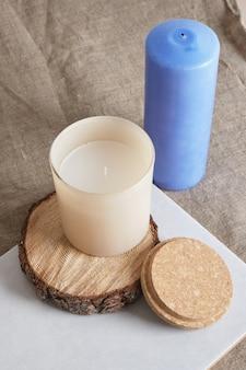 Blauwe en beige aromakaars in een glas op een houten podium van een zaag die uit een boom is gesneden. natuurlijke kaarsen voor aromatherapie kopieer ruimte