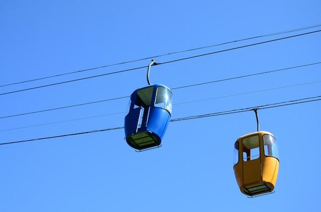 Blauwe en gele passagier kabelbaan hutten in de heldere hemel