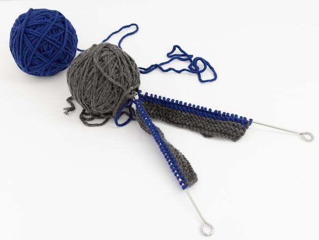 Blauwe en grijze ballen van wol met breinaalden op witte achtergrond