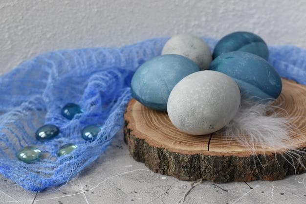 Blauwe en grijze eieren op een houten standaard met glasstenen