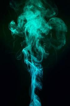Blauwe en groene rook verspreid over zwarte achtergrond