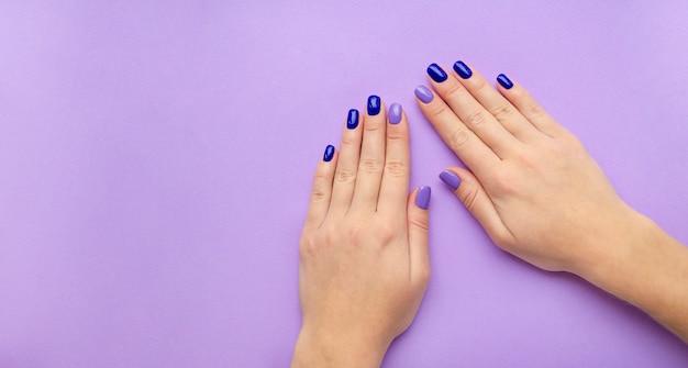 Blauwe en lila manicure op handen van de vrouw