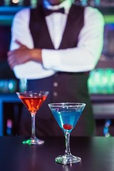 Blauwe en oranje glazen cocktail op barteller en barman