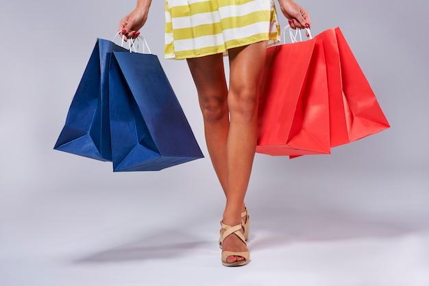 Blauwe en rode boodschappentassen die door een vrouw worden vastgehouden