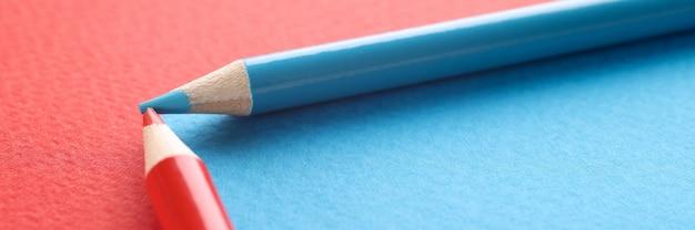 Blauwe en rode potloden op rode en blauwe achtergrond