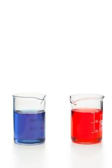 Blauwe en rode vloeistof in bekers