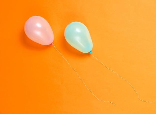 Blauwe en roze ballonnen op oranje achtergrond