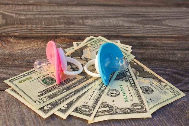 Blauwe en roze fopspenen op de achtergrond van geld.