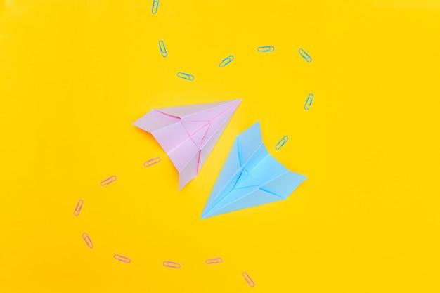 Blauwe en roze papieren vliegtuigen op een gele achtergrond