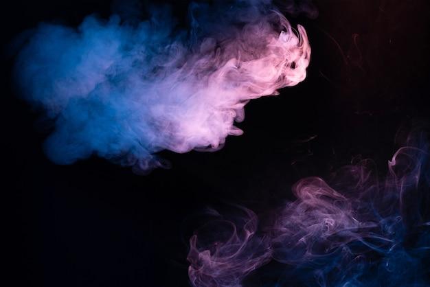 Blauwe en roze stoom op een zwarte achtergrond. ruimte kopiëren.