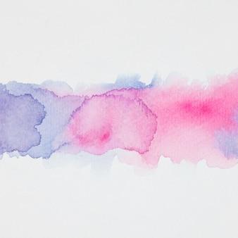 Blauwe en roze vlekken van verven op wit papier