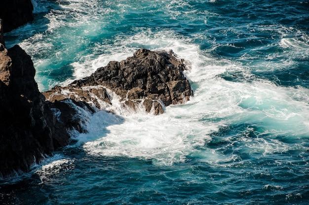 Blauwe en stormachtige diepe zee met witte golven en schuim rond de rots op zonnige dag