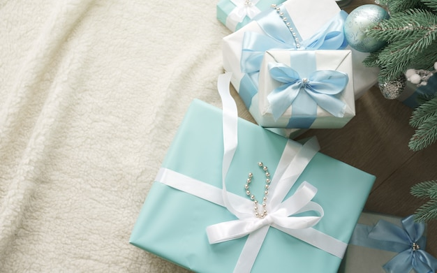 Blauwe en witte geschenkdozen onder de kerstboom