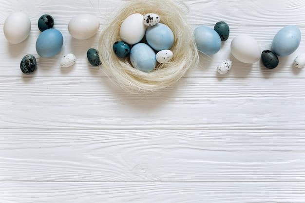 Blauwe en witte paaseieren in nest op witte houten achtergrond.