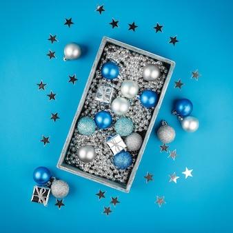 Blauwe en zilveren kerstballen, zilveren kerstparels in een houten doos op blauw. plat leggen. feestelijke rand voor wenskaart