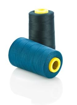 Blauwe en zwarte draden op klosjes