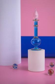Blauwe fles met parfum op een wit podium op een roze achtergrond en kolommen. cosmetica presentatie. mockup van blauwe glazen fles met parfum of olie voor reclamebanner