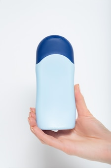 Blauwe fles voor cosmetisch product in een vrouwelijke hand. witte achtergrond