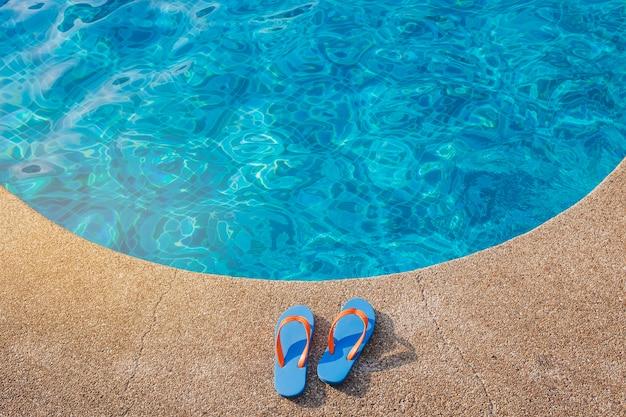 Blauwe flip-flops dichtbij het zwembad