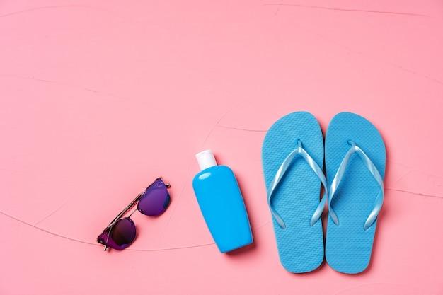 Blauwe flip-flops met zonnebrandcrème en zonnebril op roze, plat leggen
