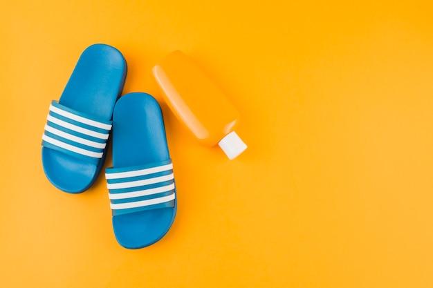 Blauwe flip-flops met zonnebrandcrème lotion fles op gele achtergrond