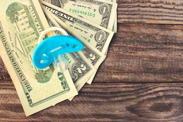 Blauwe fopspeen op de achtergrond van geld. getinte afbeelding.