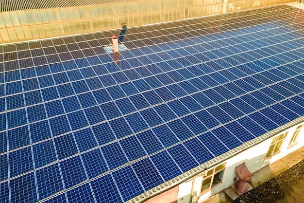 Blauwe fotovoltaïsche zonnepanelen gemonteerd op het dak van een industrieel gebouw voor het produceren van schone ecologische elektriciteit. productie van hernieuwbare energieconcept.