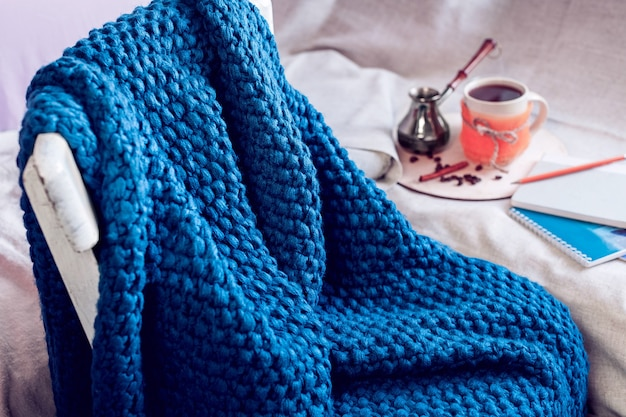 Blauwe gebreide plaid op een stoel en koffie met cezve