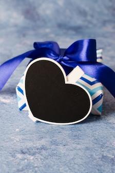 Blauwe geschenkdoos met lint. hartvormig bord met exemplaarruimte.