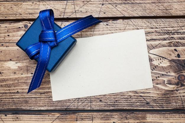 Blauwe geschenkdoos met linten en ruimte voor tekst op houten tafel.
