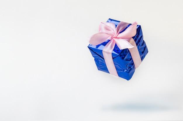 Blauwe geschenkdoos met roze lint vliegen op witte achtergrond.