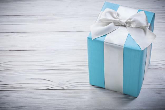 Blauwe geschenkdoos op een houten bord