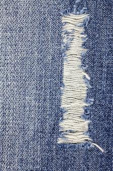 Blauwe gescheurde denim jeanstextuur Premium Foto