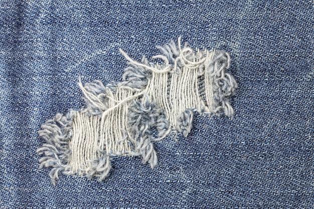 Blauwe gescheurde denim jeanstextuur