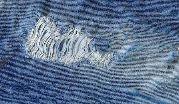 Blauwe gescheurde grunge de textuurachtergrond van denimjeans