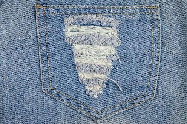 Blauwe gescheurde jeanstextuur