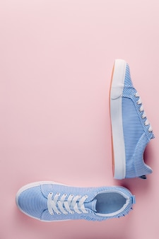 Blauwe gestreepte sneakers op roze pastel achtergrond