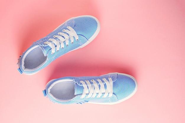 Blauwe gestreepte vrouwelijke sneakers op pastel roze achtergrond. plat leggen, bovenaanzicht